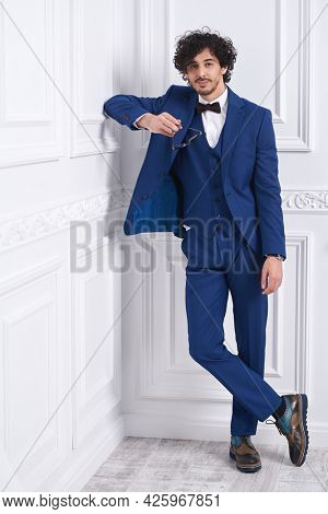 Men's style. Good-looking handsome man in elegant blue suit and a bow-tie poses in white classic apartments. Full length portrait.