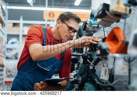 Hardware Store Supervisor Checking The Markings On Power Tools.