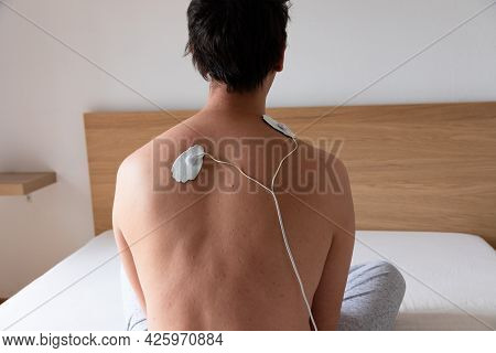 Close Up Of A Man Using A Muscle Stimulator Machine On His Back And Neck Area Using Two Electrode Pa