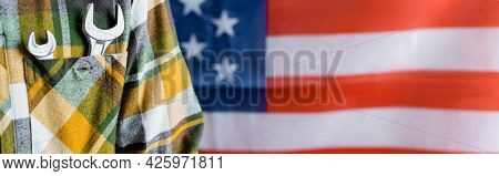 Partial View Of Workman In Plaid Shirt With Wrenches In Pocket Near Usa Flag On Blurred Background,