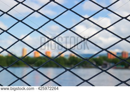 Close-up Of Grey Metal Mesh With Rhombus Pattern With Blurred Background.