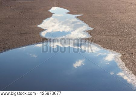 White Clouds And Sky Are Reflected In A Puddle On The Asphalt On The Road.