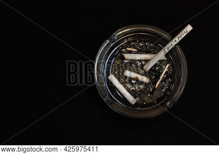 An Ashtray Full Of Cigarette Butts In Close-up On A Black Background.