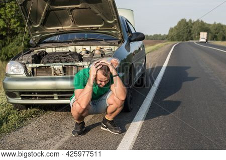 An Unfortunate Driver Is In Shock Near A Broken Car In The Middle Of The Highway. A Broken Car With