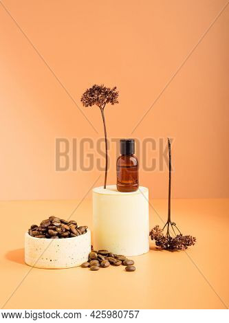 A Brown Glass Bottle With Coffee Essential Oil On A Pedestal And Coffee Beans. Pastel Beige Backgrou