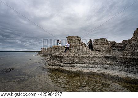June 6, 2021 - Borgholm, Sweden: People Enjoy Beautiful Limestone Formations With A Dramatic Sky In