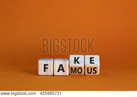 Fake Famous Symbol. Turned The Wooden Cube And Changed The Word Fake To Famous. Beautiful Orange Bac