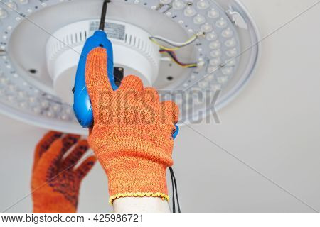 An Electrician Installs A Chandelier On The Ceiling. Hands Of An Electrician Installing Or Repairing