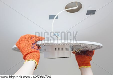 An Electrician Installs A Chandelier On The Ceiling. Hands Of An Electrician Installing And Connecti