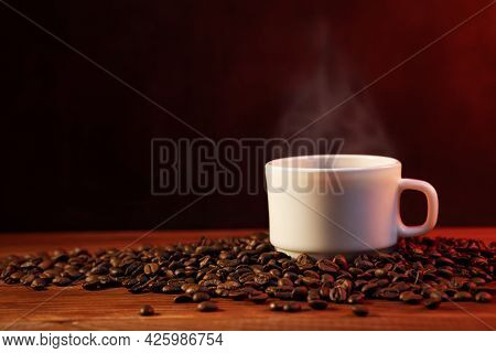 Warm Cup Of Coffee And Coffee Beans On Dark Background. Coffee Cup And Coffee Beans On Wooden Table.