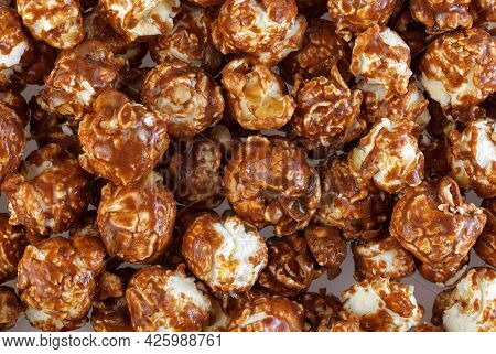 Heap Of Delicious Popcorn Covered With Milk Chocolate On White Background . A Pile Of Popcorn Textur