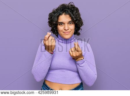 Young hispanic woman with curly hair wearing casual clothes doing money gesture with hands, asking for salary payment, millionaire business
