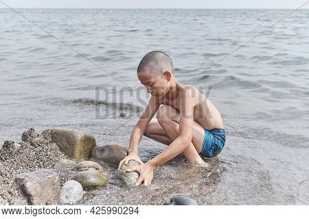 Cute Little Tanned Asian Boy Playing On The Beach, Building A Fortification Of Sand And Stones