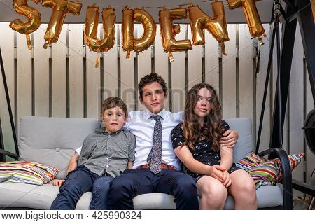 Siblings In Sofa Outdoors With Big Brother In The Middle After Graduation Cermony, Golden Balloons A