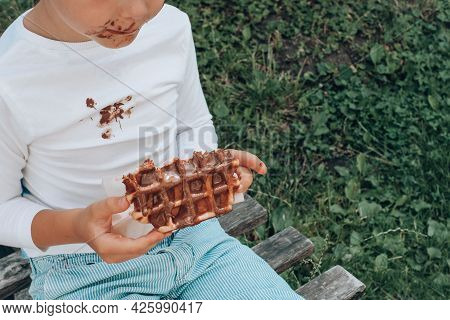 Children's Hands Holding A Belgian Waffle With Chocolate Topping. Outdoor