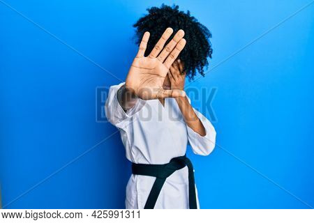 African american woman with afro hair wearing karate kimono and black belt covering eyes with hands and doing stop gesture with sad and fear expression. embarrassed and negative concept.