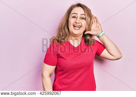 Middle age caucasian woman wearing casual clothes waiving saying hello happy and smiling, friendly welcome gesture
