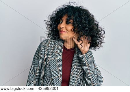 Young hispanic woman wearing business clothes smiling with hand over ear listening and hearing to rumor or gossip. deafness concept.