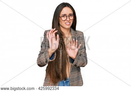 Young hispanic girl wearing business clothes and glasses disgusted expression, displeased and fearful doing disgust face because aversion reaction. with hands raised