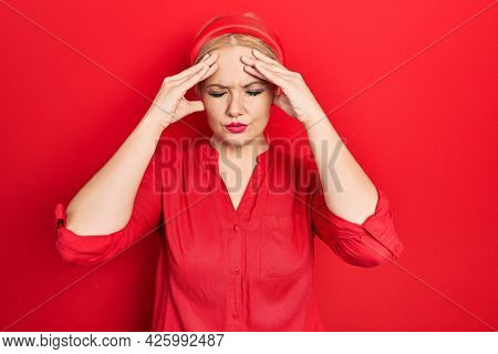 Young blonde woman wearing casual red shirt suffering from headache desperate and stressed because pain and migraine. hands on head.