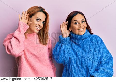 Latin mother and daughter wearing casual clothes smiling with hand over ear listening and hearing to rumor or gossip. deafness concept.