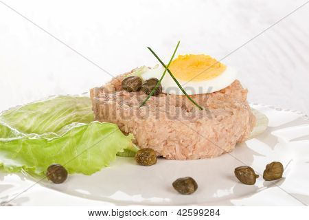 Delicious tuna on white plate with capers hard boiled egg and lettuce salad. Culinary seafood eating. poster