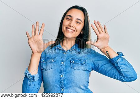 Young hispanic woman wearing casual denim jacket showing and pointing up with fingers number ten while smiling confident and happy.