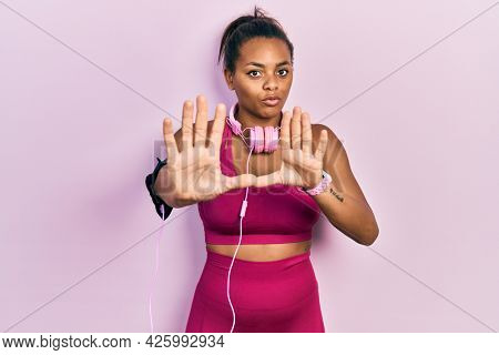 Young african american girl wearing gym clothes and using headphones moving away hands palms showing refusal and denial with afraid and disgusting expression. stop and forbidden.