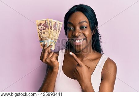 Young african american woman holding hungarian forint banknotes smiling happy pointing with hand and finger