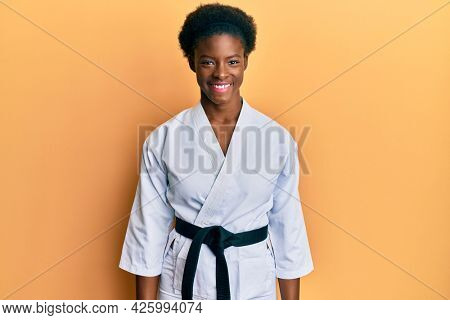 Young african american girl wearing karate kimono and black belt with a happy and cool smile on face. lucky person.