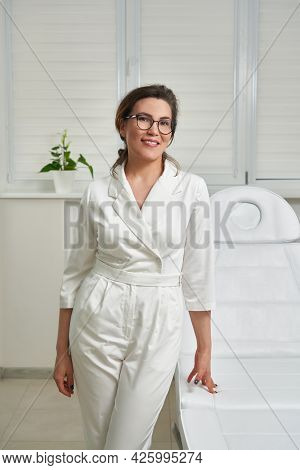 Portrait Of Smiling Cosmetologist In White Uniform Standing At Empty Massage Table In Salon