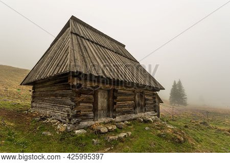 Chocholowska Valley On A Misty Spring Day. A Clearing With Shepherd Huts And Shacks. Tatra Mountains