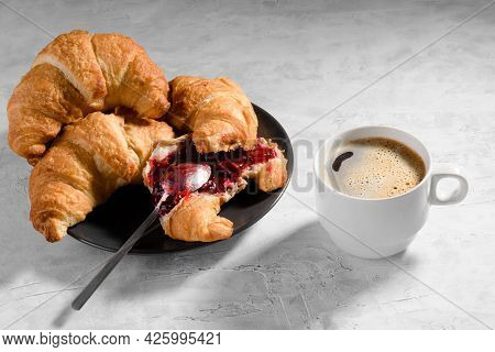 Fresh French Croissant With Cherry Jam On Grey Plate And Cau Of Fresh Coffee On Gray Background, One