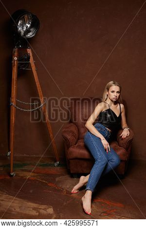 Model Girl With Bright Makeup Wearing Blue Jeans And A Black Top Sits In A Vintage Armchair. A Young