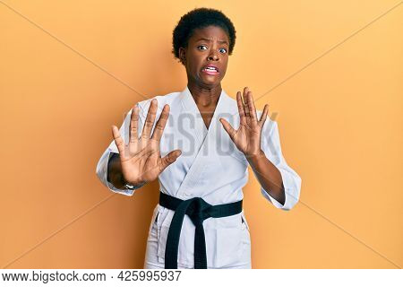 Young african american girl wearing karate kimono and black belt afraid and terrified with fear expression stop gesture with hands, shouting in shock. panic concept.