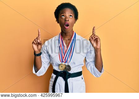 Young african american girl wearing karate kimono and black belt amazed and surprised looking up and pointing with fingers and raised arms.