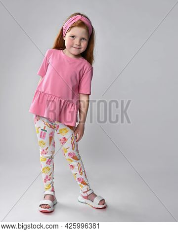 Cutie Little Red-haired Girl Touching Dress, Looking At Clothes Showing Summer Fashion Look. Adverti