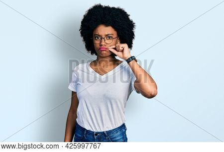 Young african american woman wearing casual white t shirt mouth and lips shut as zip with fingers. secret and silent, taboo talking