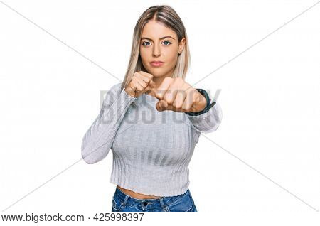 Beautiful blonde woman wearing casual clothes punching fist to fight, aggressive and angry attack, threat and violence