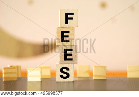 Wooden Blocks With The Word Fees And Randomly Scattered Cubes. Fixed Price Charged For A Specific Se