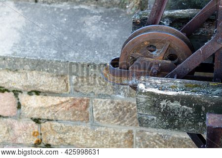 The Mechanism Of The Old Dam. Rusty Wheel In The Dam Mechanism. The Brick Support Of The Dam Is Over