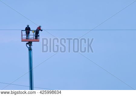Two Electricians In A Lifting Cradle Are Repairing Power Wires Against The Sky. Repair Of Wires At H