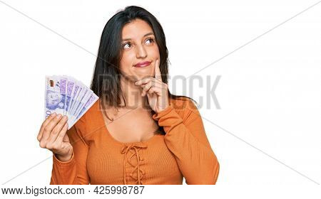 Beautiful hispanic woman holding 20 swedish krona banknotes serious face thinking about question with hand on chin, thoughtful about confusing idea