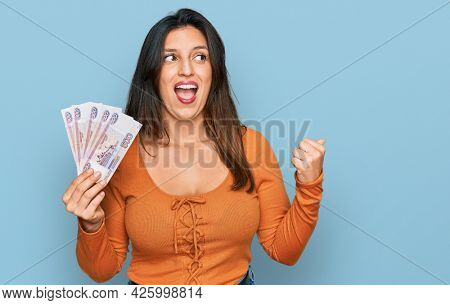 Beautiful hispanic woman holding russian 500 ruble banknotes pointing thumb up to the side smiling happy with open mouth