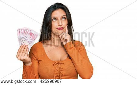 Beautiful hispanic woman holding 50 turkish lira banknotes serious face thinking about question with hand on chin, thoughtful about confusing idea