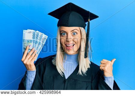 Beautiful blonde woman wearing graduation cap and ceremony robe holding hungarian forint pointing thumb up to the side smiling happy with open mouth