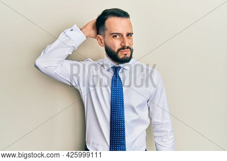 Young man with beard wearing business tie confuse and wonder about question. uncertain with doubt, thinking with hand on head. pensive concept.
