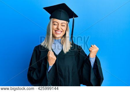 Beautiful blonde woman wearing graduation cap and ceremony robe excited for success with arms raised and eyes closed celebrating victory smiling. winner concept.