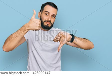 Young man with beard wearing casual white t shirt doing thumbs up and down, disagreement and agreement expression. crazy conflict