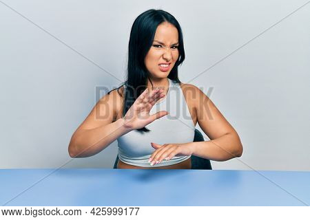 Beautiful hispanic woman with nose piercing sitting on the table disgusted expression, displeased and fearful doing disgust face because aversion reaction. with hands raised